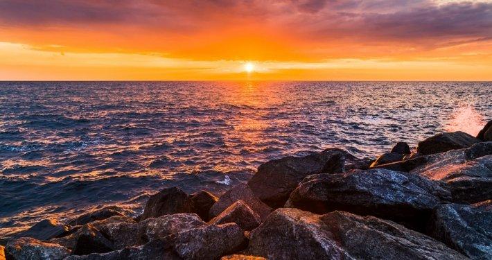 Sonnenuntergang an Steinküste vom Meer